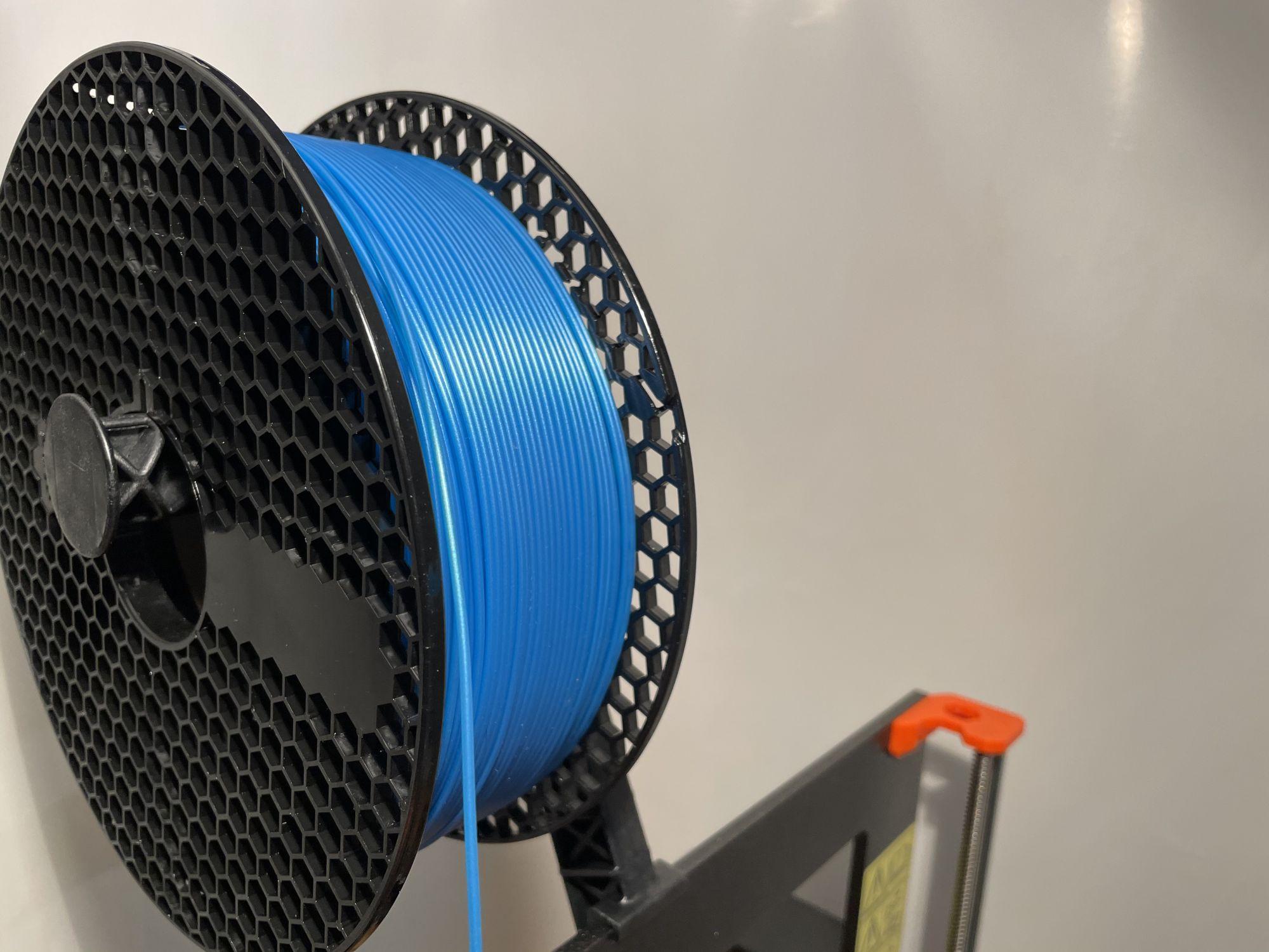 Blauer drahtförmiger Kunsstoff auf einer schwarzen Spule gewickelt